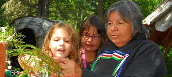 A First Nation interpreter explains the cedar medicine to two young visitors