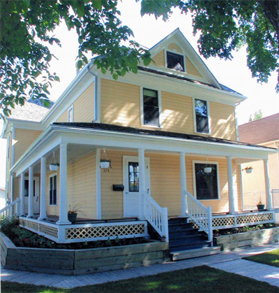 general view of the maison gabrielle roy showing the shiplap siding painted yellow to offset - Maison Canada