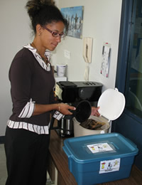 An employee emptying used coffee filters into the in-house composting bin at Parks Canada's Western and Northern Service Centre Winnipeg