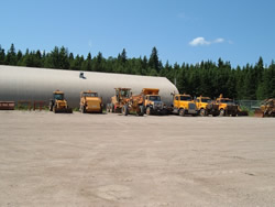 A row of heavy machinery equipment that uses biodiesel in Riding Mountain National Park lined up along the far side of a dirt parking lot.