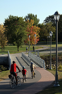 Several site visitors biking along the beautiful bike paths , crossing a bridge that covers the Lairet River in Cartier-Brébeuf National Historic Site.