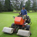 A worker mows the lawn of the golf course with a lawnmower using biofuel in Riding Mountain National Park.