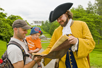 Photo of visitor and costumed interpreter in period costume at Forges du Saint-Maurice National Historic Site