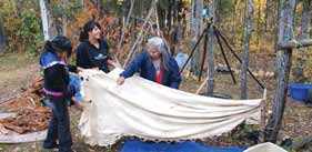Elder Elsie Marcellais of Nahanni Butte instructs youth on preparation of a Moose hide