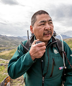 Parks Canada employee talking on a two-way radio, mountains and fields in the background.