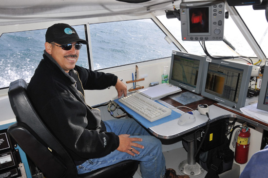 Hydrographer Roger Cameron at work station aboard launch Kinglett en route to O'Reilly Island
