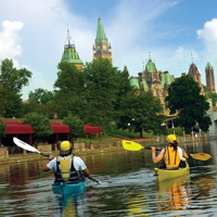 Two kayakers paddle on the Rideau Canal in Ottawa beside the National Arts Centre. A large American recreational boat (the Integrity) is visible as is the Peace Tower and East Block of Parliament Hill.