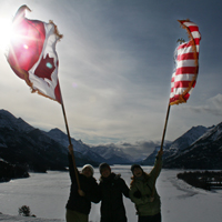 Three smiling females hold a Canadian and American flag into the wind. A frozen lake is present in the background between mountains.