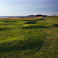 Grassy mounds in foreground with reconstructed sod houses, two visitors, and ocean in background.