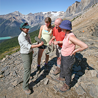 Female Parks Canada employee shows fossil to three visitors: a man and two women.