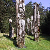 Six totem poles in forest clearing.