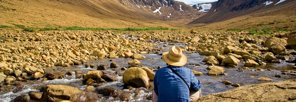 Man sitting by stream with back to camera facing orange rocks, mountains, and patches of snow.