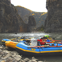 Three rafts on rocky beach in forground with river and tall clifs in background.