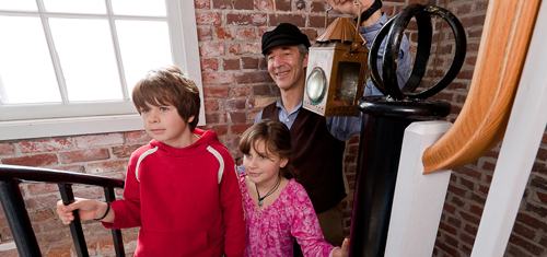 An interpreter dressed as a lighthouse keeper carrying a copper lantern, going up a spiral stair case with a seven year boy and nine year old girl in front of him.