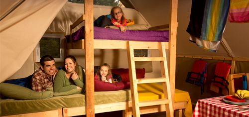 Parents laying in the bottom bunk bed of an oTENTik tent while their two children are playing on the smaller top bunk bed.
