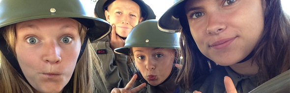 A selfie of three young girls and a boy, making funny faces and wearing dress-up WWII military helmets and jackets