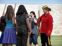 A costumed guide teaches children a NWMP drill