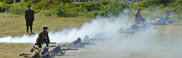 group of people in historic military uniforms firing muskets across a field