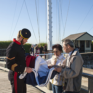 Tour guide showing visitors a flag at the Halifax CItadel National Historic Site