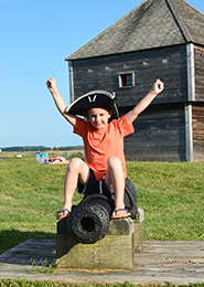Boy playing on a cannon at Fort Edward National Historic Site of Canada