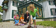 Kids playing marbles infront of the historic house