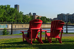 Two red chairs installed on the shore at Lachine Canal