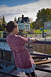 A girl clinging to the fence at locks Nos. 1-2-3 of Chambly Canal