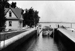 A Barge entering lock number 3 of the Chambly Canal. To the left, a lockhouse built in Neo-Queen-Anne style.