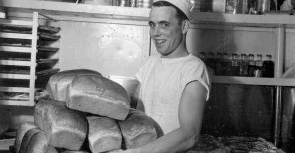 Photo of baker in galley of HMCS Haida with many loaves of bread