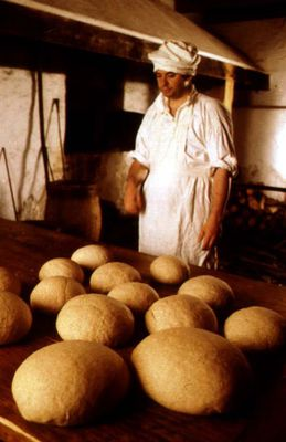 Photo of a baker standing with bread loaves and oven, Fortress of Louisbourg National Historic Site