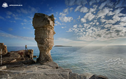 A photographer admires the rock stacks on Flowerpot Island in Fathom Five National Marine Park