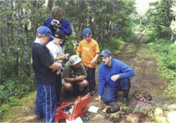 Parks Canada biologist with a Newfoundland Marten under anaesthesia, explaining his work to 2 adults and 3 children.