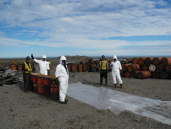 5 workers pose as they prepare to process waste fuel drums they've collected from around the site.