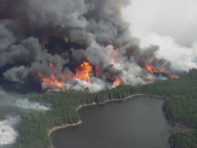 Crown fire with grey and white smoke rages near a lake
