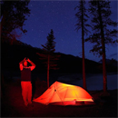 A park visitor stands outside his tent and observes the dark skies with his binoculars at one of Jasper National