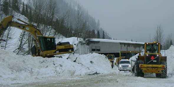 Parks Canada highway crews clean up avalanche debris covering the road.