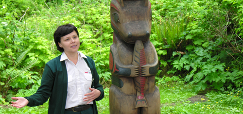 A Parks Canada interpreter standing next to a post on the Nuu-chah-nulth Trail