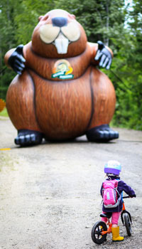 child on bicycle looking at giant inflatable Parks Canada beaver