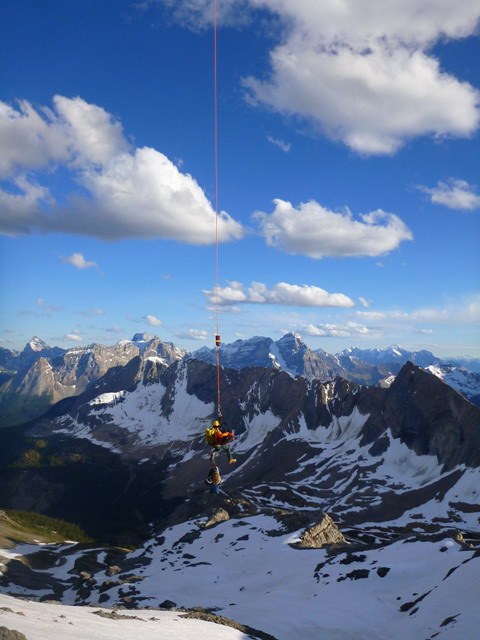 A Parks Canada Visitor Safety Specialist heli-slings the injured subject to the staging area.