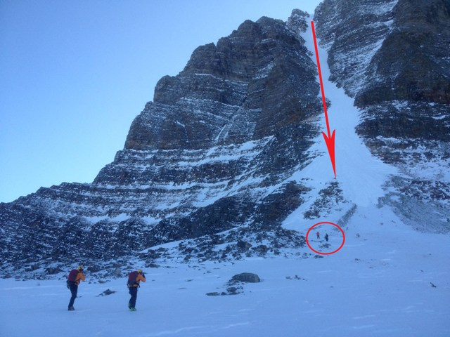 Two VS Specialists approach the accident scene.  The red arrow shows the approximate line of the skiers fall.