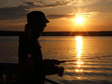 A woman fishing near sunset in Cape Breton Highlands National Park