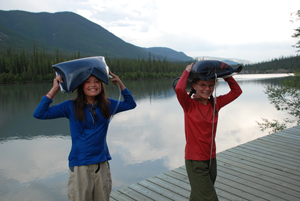 Two young visitors carry water back to their campsite in Nahanni National Park Reserve of Canada.