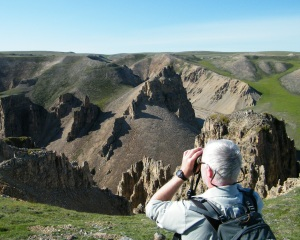 man looking at cliffs through binoculars