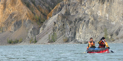 Two park visitors canoe through False Canyon on the South Nahanni River in Nahanni National Park Reserve of Canada.
