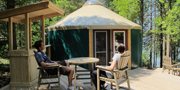 Two visitors sit infront of a Yurt