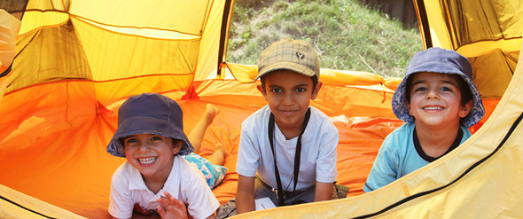 Three boys enjoy the camping experience inside a tent.