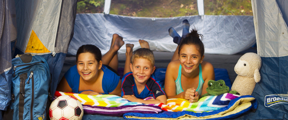 Three children in a tent looking at us, smiling.