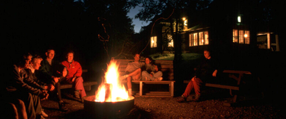 Several visitors sit up around a campfire in front of the Wabenaki Lodge.
