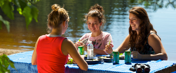 Three girls smiling as they picnic at a table by the lake.