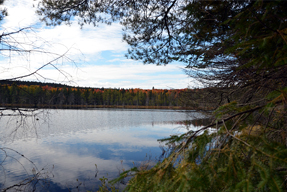 The lake is bordered by green conifers and brightly coloured deciduous trees.